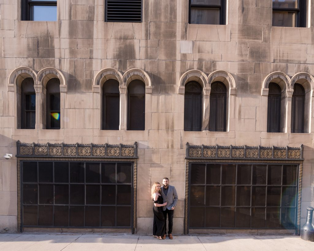 A happily engaged couple leans on a building in downtown Chicago.