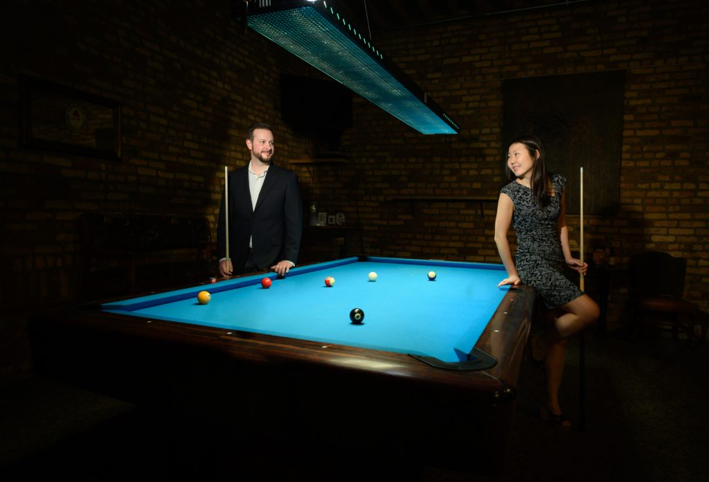 Couple poses on a billiards table for engagement photos.
