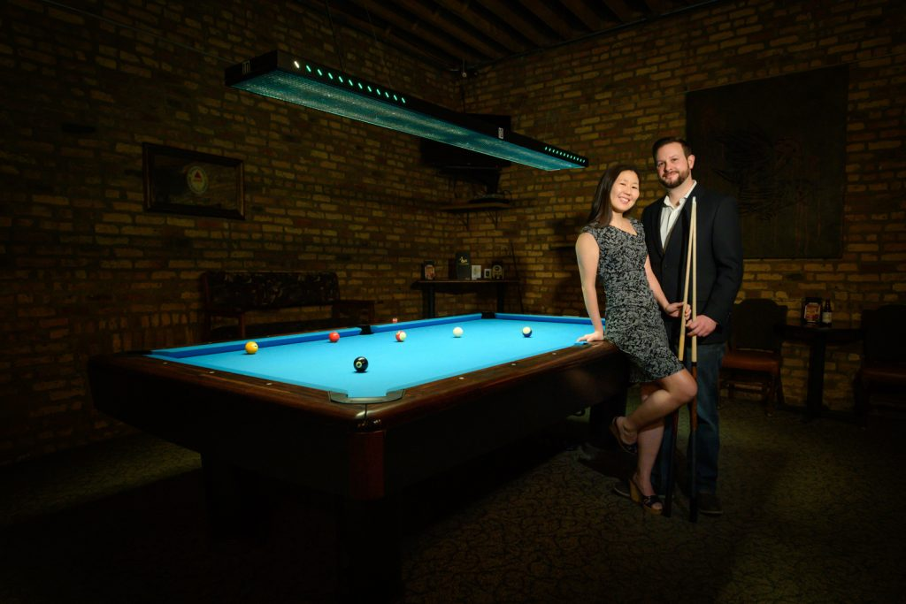 Couple poses in front of billiards table at G Cue in downtown Chicago.
