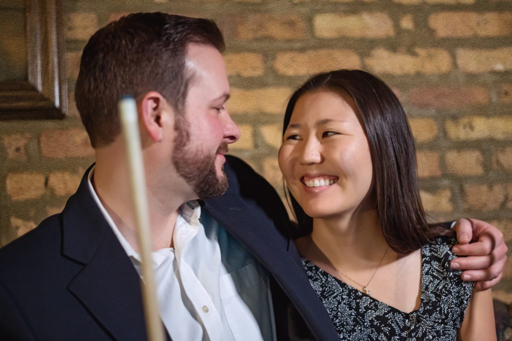 Woman smiles at her fiancé while playing pool.