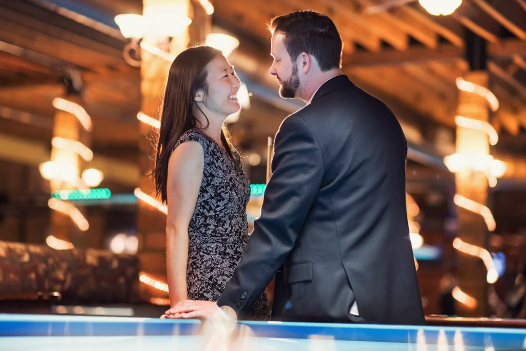 Man looks lovingly at fiancé while leaning on billiards table.