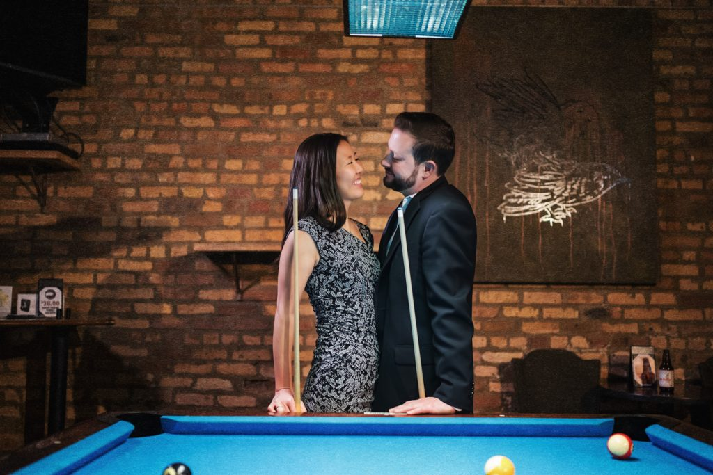 Couple looks into each others' eyes while playing billiards for Chicago engagement photos.