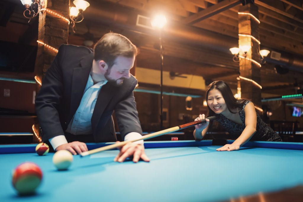 Man holds pool que for fiancé while playing billiards during Chicago engagement photoshoot.