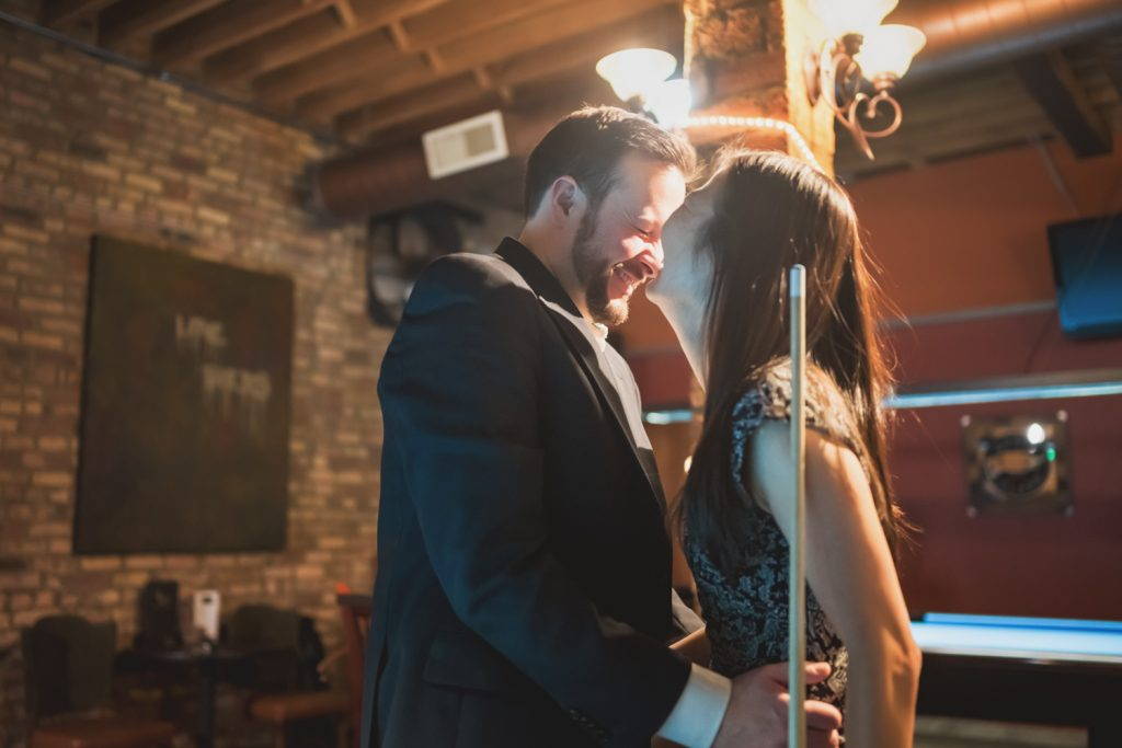 Engaged couple laughs while playing billiards while taking engagement photos in Chicago.